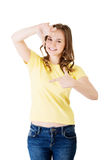 Smiling woman wearing red blouse is showing frame by hands. Stock Photo