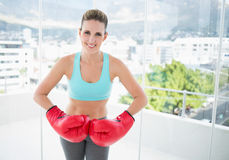Smiling woman wearing red boxing gloves Royalty Free Stock Images