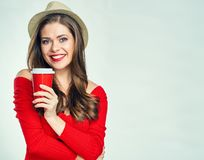 Smiling woman wearing red sweater holding coffee cup. Stock Photo