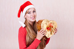 Smiling woman wearing Santa Claus hat holding gift Stock Photography