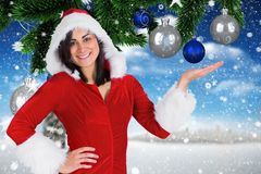 Smiling woman wearing santa costume pretending to hold digitally generated christmas baubles. Portrait of smiling woman wearing santa costume pretending to hold Royalty Free Stock Photo