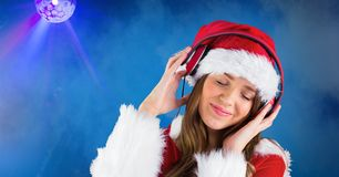 Smiling woman wearing Santa hat while listening music against blue background Stock Image