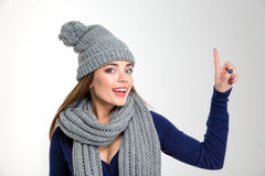Smiling woman wearing in scarf and hat pointing finger up Royalty Free Stock Image