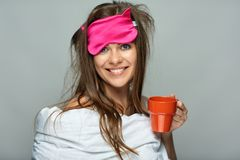 Smiling woman wearing sleep mask holding red coffee cup. Insomnia concept Stock Photos