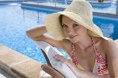 Smiling woman wearing sun hat and laying on lounge chair at poolside Royalty Free Stock Photos