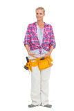 Smiling woman wearing a tool belt in ballerina pose Royalty Free Stock Image