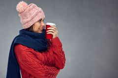 Smiling woman wearing warm clothes with winter hat holding red c Royalty Free Stock Photos