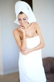 Smiling Woman Wearing White Bath Towel. With Hair Wrapped in Towel Looking Down with Hand Touching Chin Stock Images