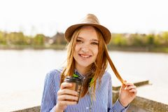 Smiling Woman Wearing White and Blue Striped Button-up Dress Shirt Holding Plastic Coffee Cup Standing Near Body of Water royalty free stock photos
