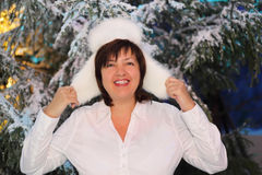 Smiling woman wearing white fur hat. Smiling middleaged woman wearing white shirt and white fur hat stand near green trees in snow Stock Photo