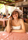 Smiling woman wearing white hat sitting at restaurant at open te Stock Photos