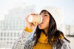 Smiling woman wearing winter clothes and drinking coffee Stock Image