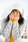 Smiling woman wearing winter clothes with hands on mouth Royalty Free Stock Photography