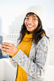 Smiling woman wearing winter clothes and holding coffee Royalty Free Stock Photo