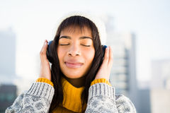 Smiling woman wearing winter clothes and listening music Royalty Free Stock Images