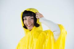 Woman wearing yellow raincoat against white background. Smiling woman wearing yellow raincoat against white background Royalty Free Stock Image