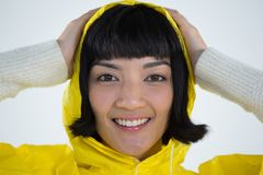 Woman wearing yellow raincoat against white background. Smiling woman wearing yellow raincoat against white background Stock Photo