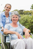 Smiling woman in wheelchair with her daughter Royalty Free Stock Photo