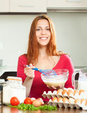 Smiling woman whipping dough in bowl Stock Photos