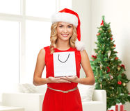 Smiling woman with white blank shopping bag. Advertisement, holydays and sale concept - smiling woman in santa helper hat with white blank shopping bag over Stock Photography