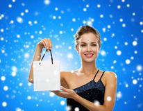 Smiling woman with white blank shopping bag. Advertisement, winter holidays, christmas and sale concept - smiling woman with white blank shopping bag over black Royalty Free Stock Image