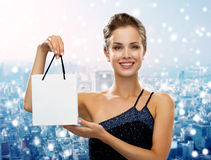 Smiling woman with white blank shopping bag. Christmas, sale, advertisement, holydays and people concept - smiling woman with white blank shopping bag over snowy Stock Images
