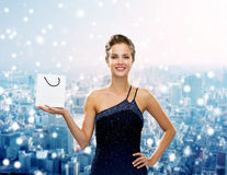 Smiling woman with white blank shopping bag. Christmas, sale, advertisement, holydays and people concept - smiling woman with white blank shopping bag over snowy Stock Photo