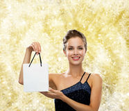 Smiling woman with white blank shopping bag. Christmas, sale, advertisement, holydays and people concept - smiling woman with white blank shopping bag over Stock Photography