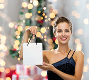 Smiling woman with white blank shopping bag. Sale, advertisement, holydays and people concept - smiling woman with white blank shopping bag over christmas tree Royalty Free Stock Image