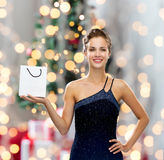 Smiling woman with white blank shopping bag. Sale, advertisement, holydays and people concept - smiling woman with white blank shopping bag over christmas tree Royalty Free Stock Photos