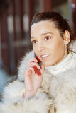 Smiling woman in white coat talking on phone Royalty Free Stock Image