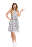 Smiling Woman In White Dotted Dress Is Pointing Royalty Free Stock Images