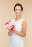 Smiling woman in white dress with bouquet of roses Stock Image