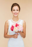 Smiling woman in white dress with bouquet of roses Stock Photos