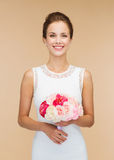 Smiling woman in white dress with bouquet of roses Royalty Free Stock Images