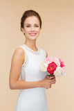 Smiling woman in white dress with bouquet of roses Royalty Free Stock Photos