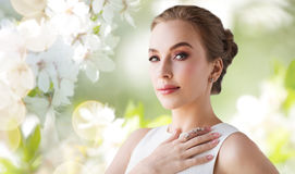 Smiling woman in white dress with diamond jewelry Stock Photography
