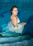 Smiling woman in white dress walking in swimming pool Royalty Free Stock Photo