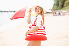 Smiling woman in white hat with red bag posing in sea beach Royalty Free Stock Photography