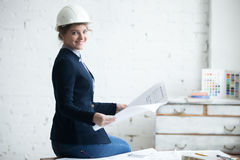 Smiling woman in white helmet with blueprint Stock Photography