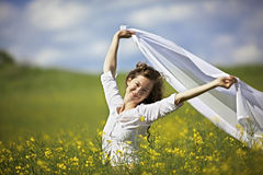 Smiling woman with white piece of cloth in wind. Young smiling woman standing in yellow rapeseed field holding a white long piece of cloth in the wind Stock Images