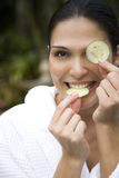 Smiling woman in a white robe with cucumbers over her eyes Royalty Free Stock Image