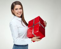 Smiling woman in white shirt holding big red gift box. Isolated portrait of happy celebrating girl Stock Photos