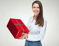 Smiling woman in white shirt holding big red gift box. Isolated portrait of happy celebrating girl Stock Images