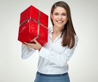 Smiling woman in white shirt holding big red gift box. Isolated portrait of happy celebrating girl Stock Image