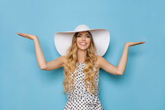 Smiling Woman In White Sun Hat Is Holding Hands Raised And Presenting Royalty Free Stock Photos