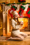 Smiling woman in white sweater warming at fireplace with hot te Royalty Free Stock Images
