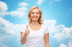 Smiling woman in white t-shirt showing thumbs up. Gesture, advertisement and people concept - smiling woman in blank white t-shirt showing thumbs up over blue Stock Images