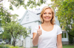 Smiling woman in white t-shirt showing thumbs up. Gesture, advertisement, real estate, home and people concept - smiling woman in blank white t-shirt showing Stock Photo