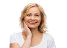 Smiling woman in white t-shirt touching her face Royalty Free Stock Photos
